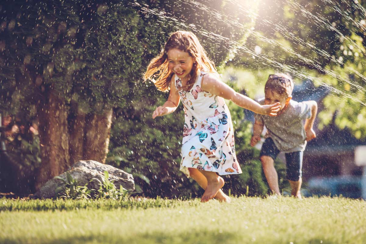 Kids running through a sprinkler on a lawn in summer